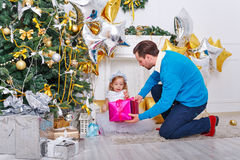 Father and daughter lay out the gifts under the Christmas tree. Royalty Free Stock Image