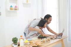 Father and daughter learning online cooking using laptop computer stock photography