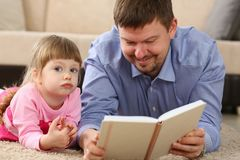 Father and daughter lie on floor reading interesting book. Together portrait stock image