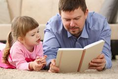 Father and daughter lie on floor reading interesting book. Together portrait royalty free stock image