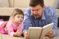 Father and daughter lie on floor reading interesting book. Together portrait stock photo