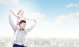 Father and daughter. Little daughter sitting on father's shoulders. Parenting concept stock image