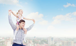 Father and daughter. Little daughter sitting on father's shoulders. Parenting concept royalty free stock images