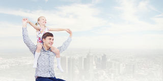 Father and daughter. Little daughter sitting on father's shoulders. Parenting concept stock photos