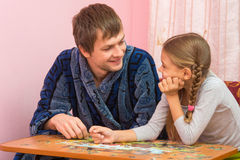 Father and daughter looked each other collecting puzzle elements Stock Image