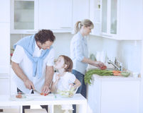 Father and Daughter looking at each other whilst preparing healthy meal in kitchen Royalty Free Stock Photo