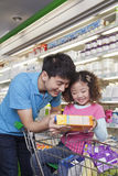 Father and Daughter Looking at Juice Box in Supermarket Royalty Free Stock Photo