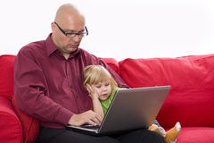 Father and daughter looking into laptop Stock Image