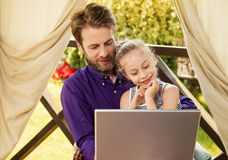 Father and daughter looking at laptop computer in the garden Royalty Free Stock Image