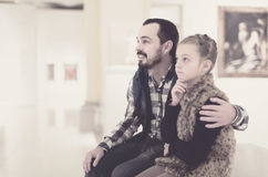 Father and daughter looking at paintings in halls of museum Stock Image