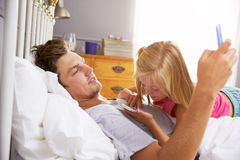 Father And Daughter Lying In Bed Using Mobile Phones Royalty Free Stock Photo