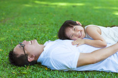 Father and daughter lying on a meadow in the park Royalty Free Stock Photography