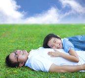 Father and daughter lying on a meadow in the park Stock Photo