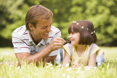 Father and daughter lying outdoors with flowers stock photography
