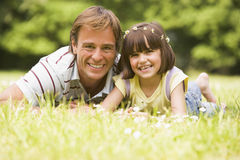 Father and daughter lying outdoors with flowers royalty free stock image