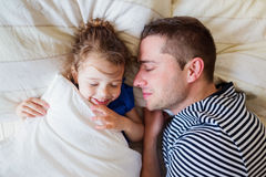 Father and daughter lying in parents bed, sleeping, smiling Stock Images