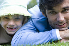 Father and daughter (5-7) lying on stomachs on grass, smiling, portrait, close-up Royalty Free Stock Image