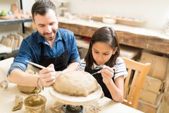 Father And Daughter Making Design On Clay Using Sculpting Tools. In ceramic class royalty free stock image
