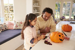 Father And Daughter Making Halloween Decorations At Home Stock Images