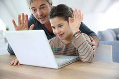 Father and daughter making video call on internet Stock Photos