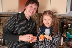 Father and daughter with mandarins on kitchen Stock Photo