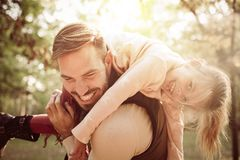 Father and daughter in meadow. Father carrying little girl on shoulders royalty free stock image