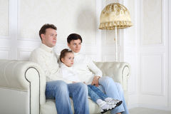 Father, daughter and mother in sweaters and jeans sit on sofa Stock Photo