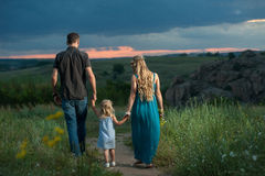 Father, daughter and mother walking outdoors Royalty Free Stock Images