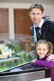 Father and daughter near layout of residential buildings. Stock Photo