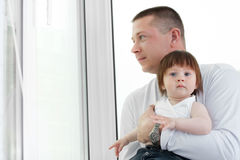 Father and daughter near window Stock Images