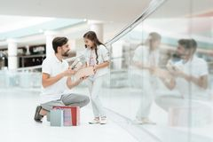 Father and daughter are opening new present for girl in shopping mall. stock photos