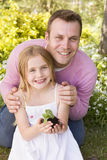 Father and daughter outdoors holding plant smiling Royalty Free Stock Photos