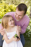Father and daughter outdoors holding plant smiling Stock Photography