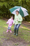 Father and daughter outdoors with umbrella smiling Royalty Free Stock Photo