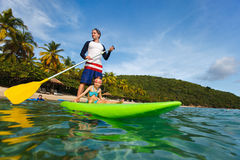 Father and daughter paddling. Father and his adorable little daughter paddling on stand up board having fun during summer beach vacation stock image