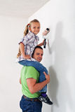 Father and daughter painting the room together Stock Photo