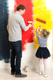 Father and daughter painting wall Stock Images