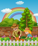 Father and daughter planting tree in garden Stock Image