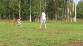 Father and daughter play with ball on green field with football gate at summer stock video footage