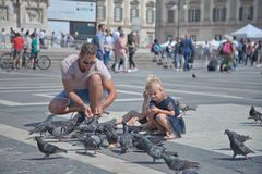 Father and daughter play with birds in Piazza Duomo in Milano