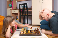 Father and daughter play chess Stock Images