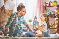 Father and daughter play. Funny time! Father and his child are playing at home. Cute girl is doing makeup to her dad, sitting on the bed in the bedroom. Family royalty free stock photo