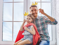Father and daughter play. Happy father`s day! Dad and his child daughter are playing and having fun together. Beautiful funny girl and daddy have crowns on royalty free stock photography