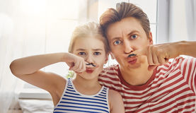 Father and daughter play. Happy father`s day! Dad and his child daughter are playing and having fun together. Beautiful funny girl and daddy have mustache on Royalty Free Stock Images