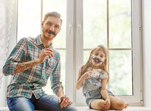 Father and daughter play. Happy father`s day! Dad and his child daughter are playing and having fun together. Beautiful funny girl and daddy have mustaches on stock photos