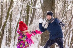 Father and daughter play snowballs in winter forest royalty free stock photography