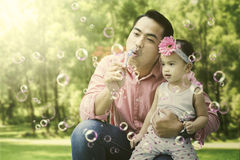 Father and daughter play soap bubbles on summer Stock Image