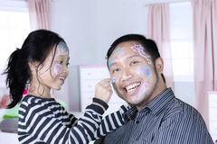 Father and daughter play together in the bedroom. Young Asian father playing with her daughter in the bedroom while painting their face with crayons Royalty Free Stock Images