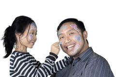 Father and daughter play together in the studio. Image of Asian father and his daughter playing with crayons while drawing their face, isolated on white Royalty Free Stock Photography