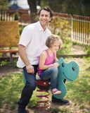 Father and daughter on playground spring rider Stock Image